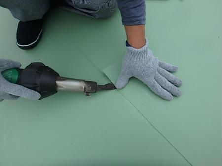 絵を書くように建物に色を塗る防水工スタッフ
